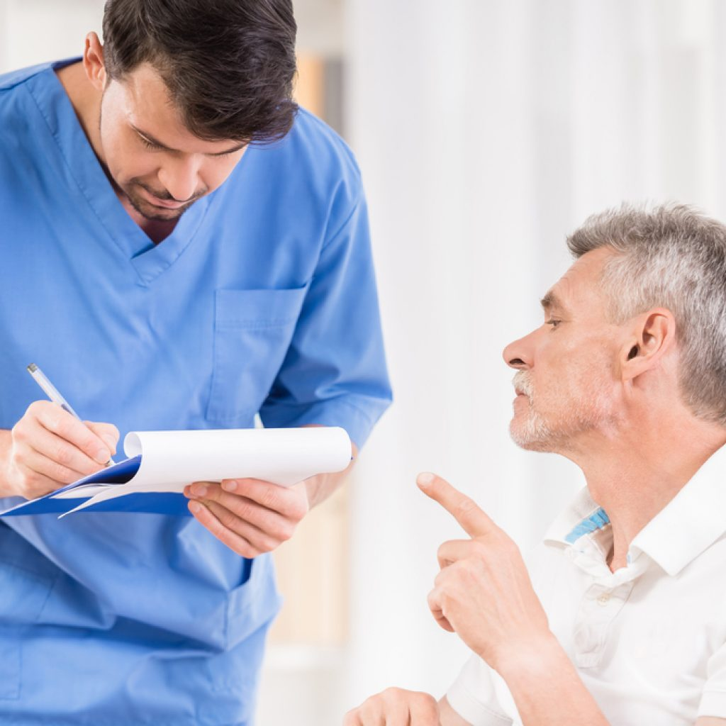 Nurse taking notes with patient